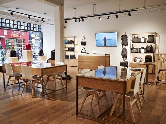 Glass topped, oak-faced birch ply display tables, illuminated shelving units, sales counter, and window display plints at Knomo at Neal Street, London - Internals