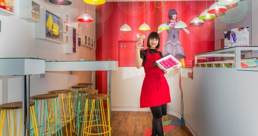 Digitally printed wall graphics, curved counter, wall displays, high level tables, coloured lamp shades, and digitally printed floor graphics at Miss Macaroon, Birmingham